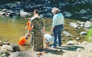 adults and children standing near a stream