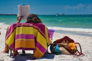 a person sitting in a chair reading a book at the beach
